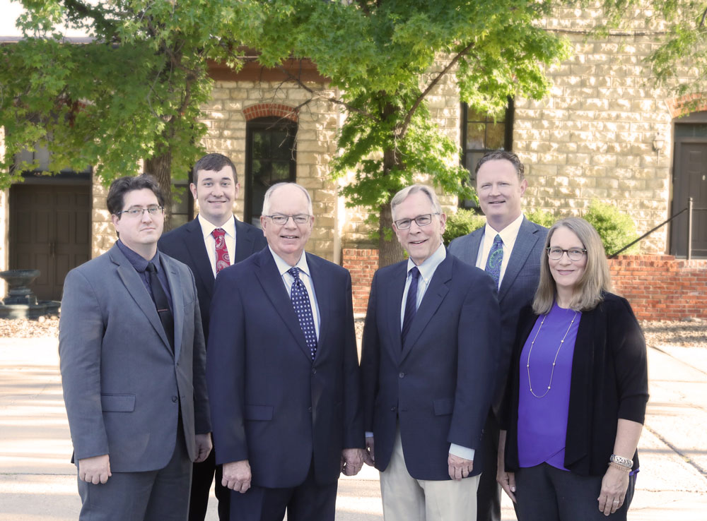 Adrian & Pankratz attorneys standing in front of the Old Mill building in Newton, Kansas